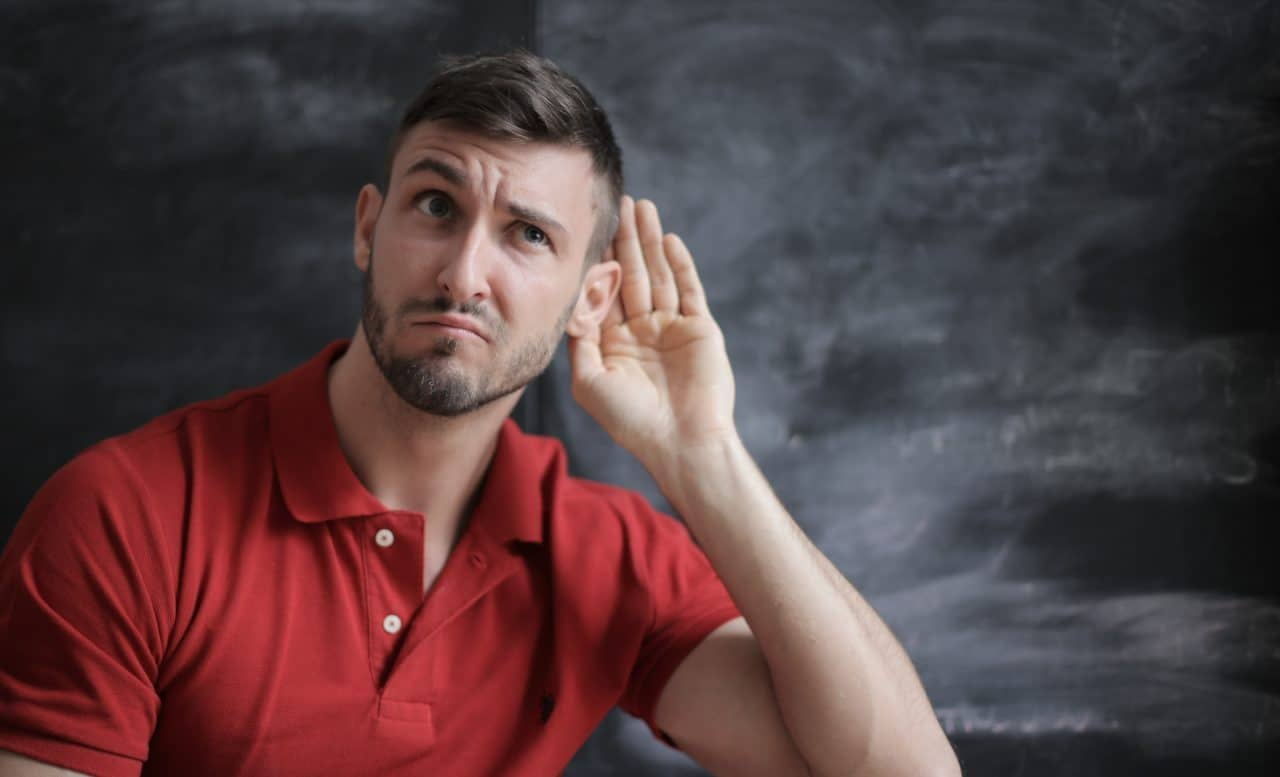 man putting hand up to ear
