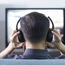 Back side of an man wearing black heaphones in front of blurry out-of-focus television and home entertainment system background