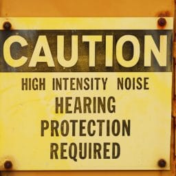 Metal caution sign for noise on industrial equipment