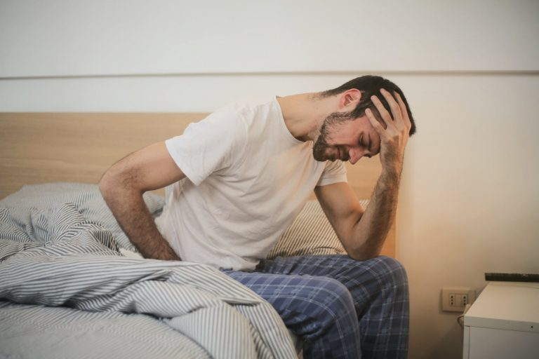 Man sits on edge of bed.